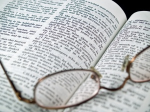 The Bible opened to the Book of Proverbs with Glasses