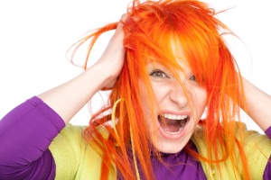 Shocked screaming woman holding red head with hands