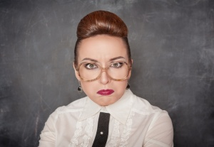 Angry teacher with eyeglasses on the school blackboard background
