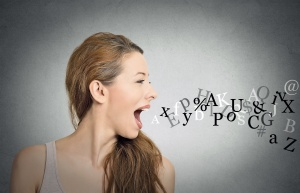 Side view portrait woman talking with alphabet letters coming out of her open mouth isolated grey wall background. Human face expressions, emotions. Communication, information, intelligence concept