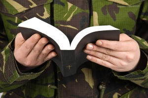 Army soldier reading bible ,selective focus on book and hands