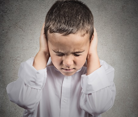 Boy Covers his Ears, hear no evil concept, grey background